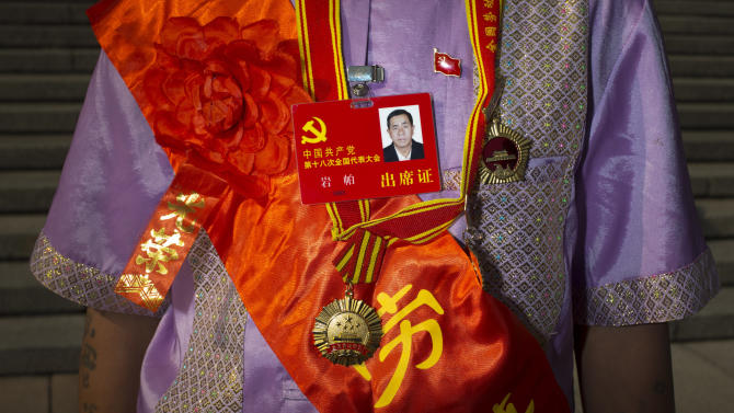 """In this Thursday, Nov. 8, 2012 photo, Communist Party delegate Yan Pa, wearing medals and a red sash emblazoned with characters """"Model Worker,"""" and """"Glory,"""" poses for photos outside the Great Hall of the People, after the opening session of the 18th Communist Party Congress in Beijing Along with government officials, managers of state industries and military officers, delegates of the 18th Communist Party Congress also include migrant workers, peasants, factory technicians, teachers, doctors, artists and Olympic gold medalists. Many of the rank and file delegates are brought to Beijing to make the roughly 2,300-member congress more representative, and have no real political clout. They ratify decisions made by a few dozen party insiders in backroom deals. Still, they believe in the cause and swoon at the prestige of being chosen to be a national delegate. (AP Photo/Alexander F. Yuan)"""