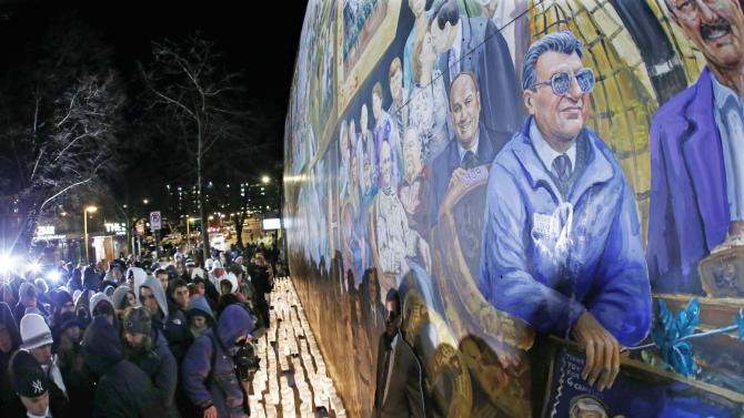 People gather in front of a mural containing a likeness of former Penn State football coach Joe Paterno, right, at a candlelight memorial on the first anniversary of his death, Tuesday, Jan. 22, 2013, in State College, Pa. (AP Photo/Gene J. Puskar)