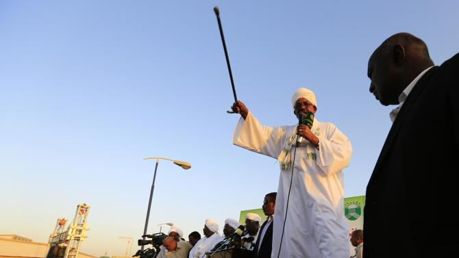 Sudanese President Omar Hassan al-Bashir waves to the crowd during a rally with Sufi supporters in Hajj Yusuf at Khartoum district