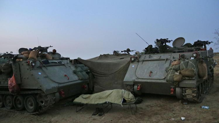 An Israeli soldier sleeps next to an armoured personnel carriers at a staging area near the Israel Gaza Strip Border, southern Israel, early Tuesday, Nov. 20, 2012. On Tuesday, grieving Gazans were burying militants and civilians killed in ongoing Israeli airstrikes, and barrages of rockets from Gaza sent terrified Israelis scurrying to take cover. Efforts to end a week-old convulsion of Israeli-Palestinian violence drew in the world's top diplomats Tuesday, with U.S. President Barack Obama dispatching his secretary of state to the region on an emergency mission and the U.N. chief appealing from Cairo for an immediate cease-fire. (AP Photo/Lefteris Pitarakis)