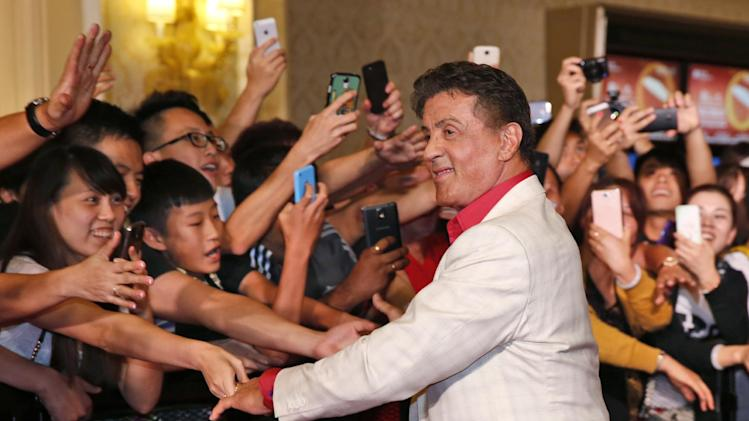 """U.S. actor Sylvester Stallone shakes hands with fans at the red carpet for the Macau premiere of his movie """"The Expendables 3"""" in Macau, China, Friday, Aug. 22, 2014. (AP Photo/Kin Cheung)"""