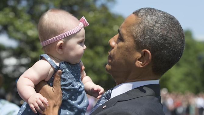 President Barack Obama holds six-month-old Olivia Hughes, of Arlington, Va., after arriving on the South Lawn of the White House in Washington, Friday, June 27, 2014, from Minnesota. (AP Photo/ Evan Vucci)