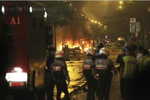 Riot policemen watch burning vehicles during a riot in Singapore's Little India district