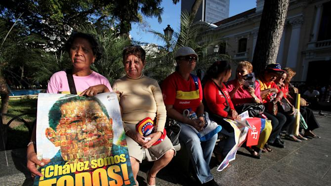 "Supporters of Venezuela's President Hugo Chavez, one of them holding a sign that reads in Spanish ""We are all Chavez,"" sit after his return to his country at Bolivar square in Caracas, Venezuela, Monday, Feb. 18, 2013. Chavez returned to Venezuela early Monday after more than two months of treatment in Cuba following cancer surgery, his government said, triggering street celebrations by supporters who welcomed him home while he remained out of sight at Caracas' military hospital. (AP Photo/Fernando Llano)"