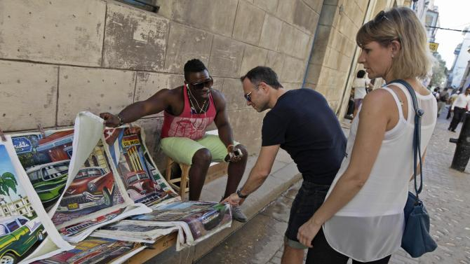 A man shows tourists prints for sale in Old Havana