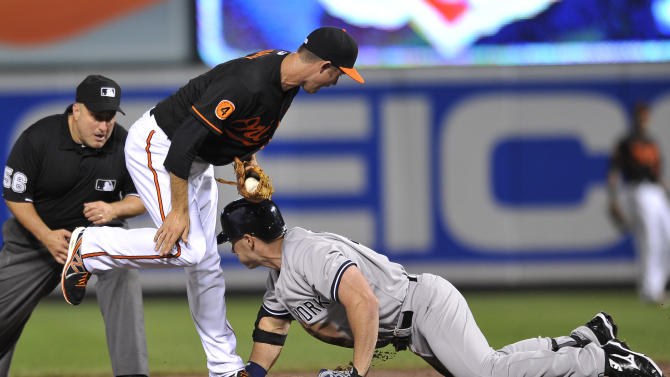 Baltimore Orioles shortstop J.J. Hardy tags out New York Yankees Travis Hafner trying to stretch a single into a double in the third inning of a baseball game, Sunday, June 30, 2013, in Baltimore. Also pictured is second base umpire Eric Cooper.(AP Photo/Gail Burton)