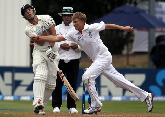 New Zealand's Rutherford reacts as England's Root reaches to field a ball, as umpire Rauf looks on, during the third day of the first test in Dunedin