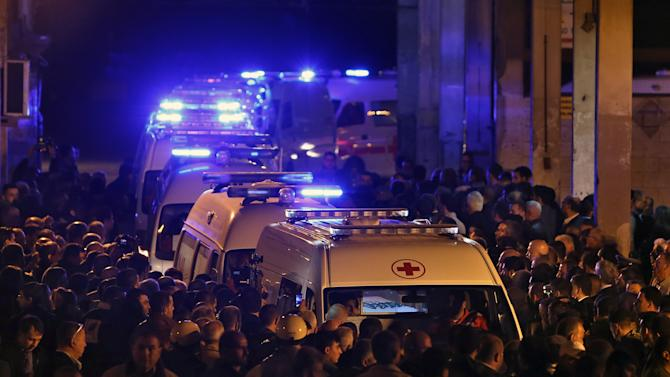 Friends and relatives of Lebanese who died when their Air Algerie flight crashed in July in a desolate part of Mali, gather near the ambulances carrying the coffins, upon their arrival at Rafik Hariri International Airport in Beirut, Lebanon, Sunday, Dec. 21, 2014. The bodies of the nineteen Lebanese nationals were among 116 people who were on the Air Algerie flight crashed in July 24, 2014, arrived at Beirut airport. Hundreds of the dead friends and relatives received them at Beirut's airport on Sunday. (AP Photo/Bilal Hussein)
