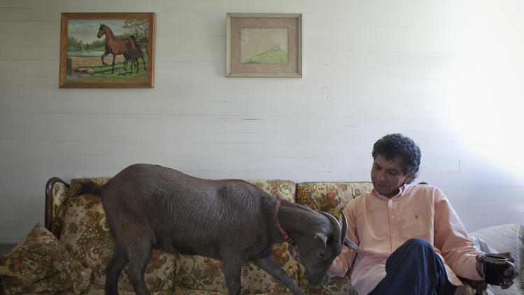 Fakroddin and his pet goat Cocoa relax at their home in Summit