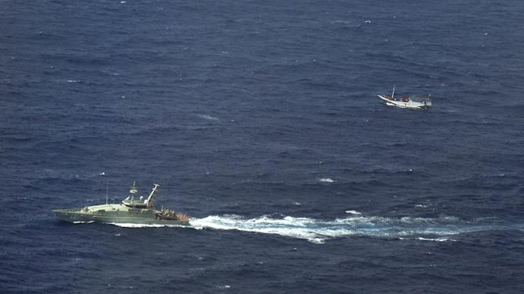 An Australian navy vessel (left) shadows a boat believed to be carrying up to 180 asylum-seekers off Indonesia, on July 4, 2012
