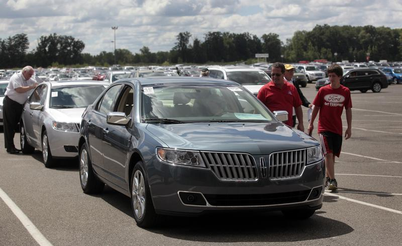 Auto dealership owners take a look at vehicles during an auto auction in Carleton