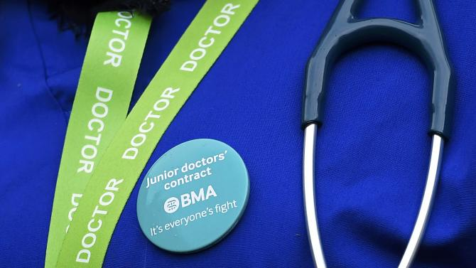 A junior doctor wears a protest badge during a strike outside St Thomas' Hospital in London