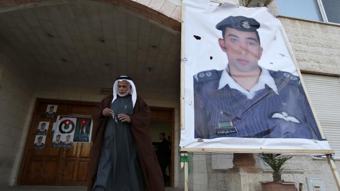 A relative of Islamic State captive Jordanian pilot Muath al-Kasaesbeh walks past a poster of Muath in front of his clan's headquarters in Amman