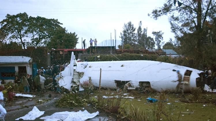 Bystanders look on as peacekeepers secure the wreckage of a crashed plane, in Goma, Congo, Monday, March 4, 2013. A Fokker airplane of the private airline CAA crashed in the city center Monday, killing at least six people onboard. There were no reported casualties on the ground.(AP Photo/Sinziana Demian)