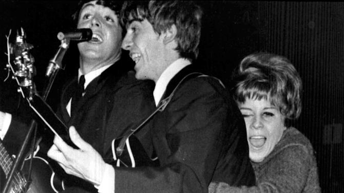 FILE - In this Oct. 26, 1963 file photo, a young fan hugs George Harrison as The Beatles play at a pop festival in Stockholm, Sweden. At left is Paul McCartney. 1963 was a year in which a number of historical events occurred. (AP Photo/File)