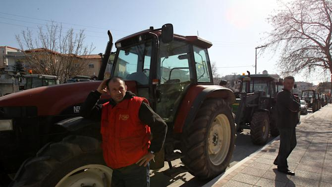 Farmers stand next to their parked tractors during a protest in the village of Epanomi, near Thessaloniki, Tuesday, Feb. 5, 2013. Farmers are threatening to block highways across the country to protest new tax laws, spending cuts and high fuel taxes. (AP Photo/Nikolas Giakoumidis)