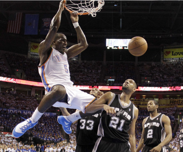 Oklahoma City Thunder center Kendrick Perkins (5) dunks in front of San Antonio Spurs' Tim Duncan (21), Boris Diaw (33), and Kawhi Leonard (2) during the first half of Game 4 in the NBA basketball pla