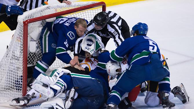 Vancouver Canucks goalie Eddie Lack, of Sweden, tangles with Calgary Flames' Brandon Bollig as Jannik Hansen (36), of Denmark, and linesman Darren Gibbs try to break them apart during the second period of Game 2 of an NHL hockey first-round playoff series, Friday, April 17, 2015, in Vancouver, British Columbia. (Jonathan Hayward/The Canadian Press via AP)