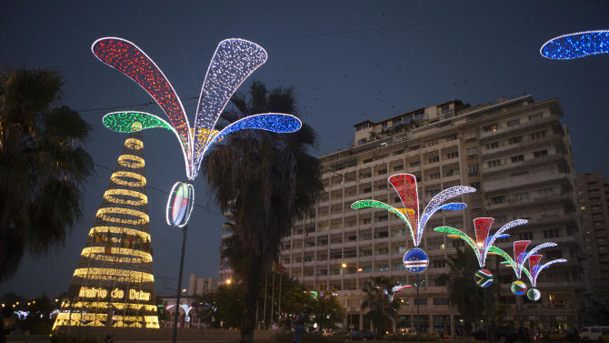 In this Tuesday, Dec. 11, 2012 photo, people walk past Christmas decorations in Independence Square in central Dakar, Senegal. As Christmas approaches in mostly Muslim Senegal, vendors ply the streets selling tinsel, artificial trees, and inflatable Santas, and the main boulevards are all aglow in holiday lights. Senegal, a moderate country along Africa's western coast, has long been a place where Christians and Muslims coexist peacefully and share in each other's holidays. (AP Photo/Rebecca Blackwell)