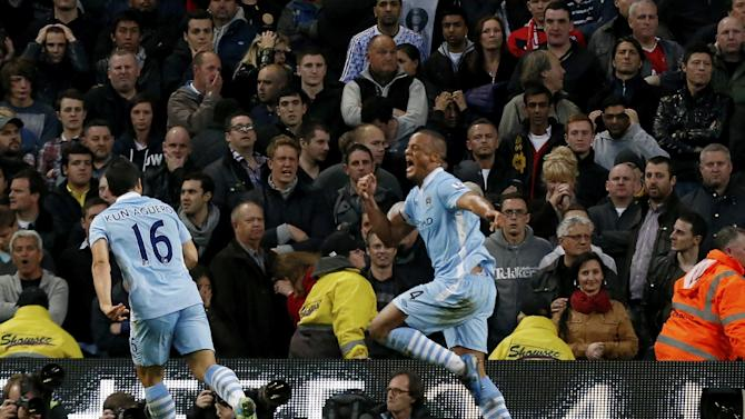 Manchester City's Vincent Kompany, right, runs past the Manchester United fans as he celebrates scoring during the English Premier League soccer match between Manchester City and Manchester United at the Etihad Stadium in Manchester, Monday, April 30, 2012.  (AP Photo/Matt Dunham)