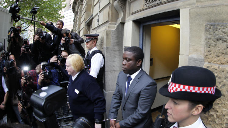 FILE-  Former city trader Kweku Adoboli, second right, leaves the City of London Magistrates' Court in London, in this file photo dated Thursday, Sept. 22, 2011, where he is accused of fraud and two charges of false accounting at Swiss banking giant UBS.  Adoboli appeared in court in London for his trial Friday Sept. 14, 2012, and prosecution lawyer Sasha Wass told a British jury that Adoboli lied to his employer, invented clients and breached the bank's safeguards against high-risk trading between 2008 and 2011. (AP Photo/Sang Tan, File)