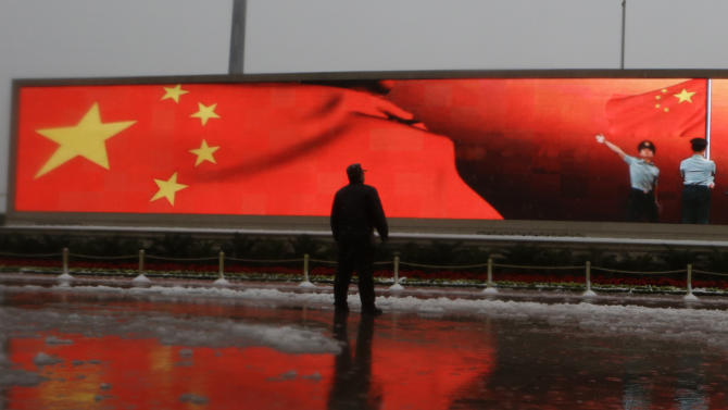 A Chinese man stands near a screen displaying the Chinese national flag and Chinese paramilitary police men performing a flag ceremony near the Great Hall of the People where the Chinese Communist Party's 18th National Congress is scheduled to begin on Nov. 8 in Beijing, China, Sunday, Nov. 4, 2012. The once-a-decade event installs a new leadership to run the world's second largest economy and newly assertive global power.  (AP Photo/Ng Han Guan)