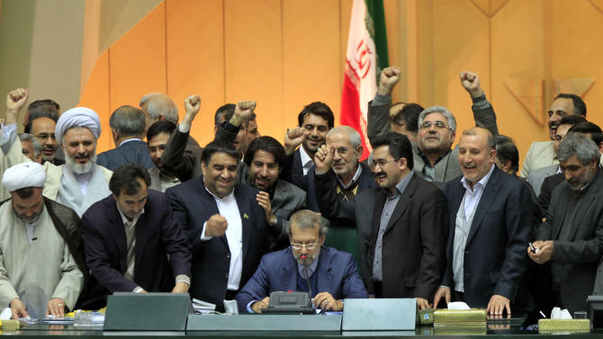 Iranian lawmakers chant slogans, as parliament speaker Ali Larijani, center, announces the votes of impeachment of labor minister, Abdolreza Sheikholeslami, unseen, in Tehran, Iran, Sunday, Feb. 3, 2013. Iranian lawmakers impeached the country's labor minister over his controversial appointment of an official implicated in the deaths of prisoners. In response, Ahmadinejad turned the tables on his conservative opponents and accused parliament speaker Ali Larijani and his relatives of misusing power. (AP Photo/Vahid Salemi)