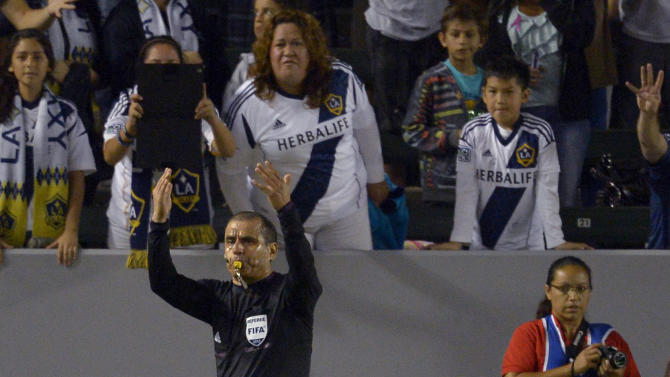 An official, top, calls for trainers as Los Angeles Galaxy's Landon Donovan lies on the ground after injuring his leg during the second half of an MLS soccer match against Real Salt Lake, Saturday, Oct. 6, 2012, in Carson, Calif. Real Salt Lake won 2-1. (AP Photo/Mark J. Terrill)