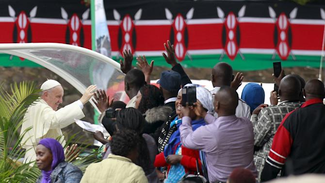 Pope Francis waves to faithful as he arrives for a Papal mass in Kenya's capital Nairobi