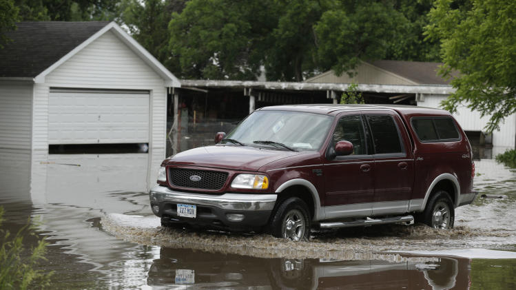 A resident drives through flood waters in front of a garage, Tuesday, June 25, 2013, in New Hartford, Iowa. Hundreds of residents obeyed an order to evacuate their homes in this northeast Iowa town Tuesday before floodwaters from a rising creek could strand them. (AP Photo/Charlie Neibergall)