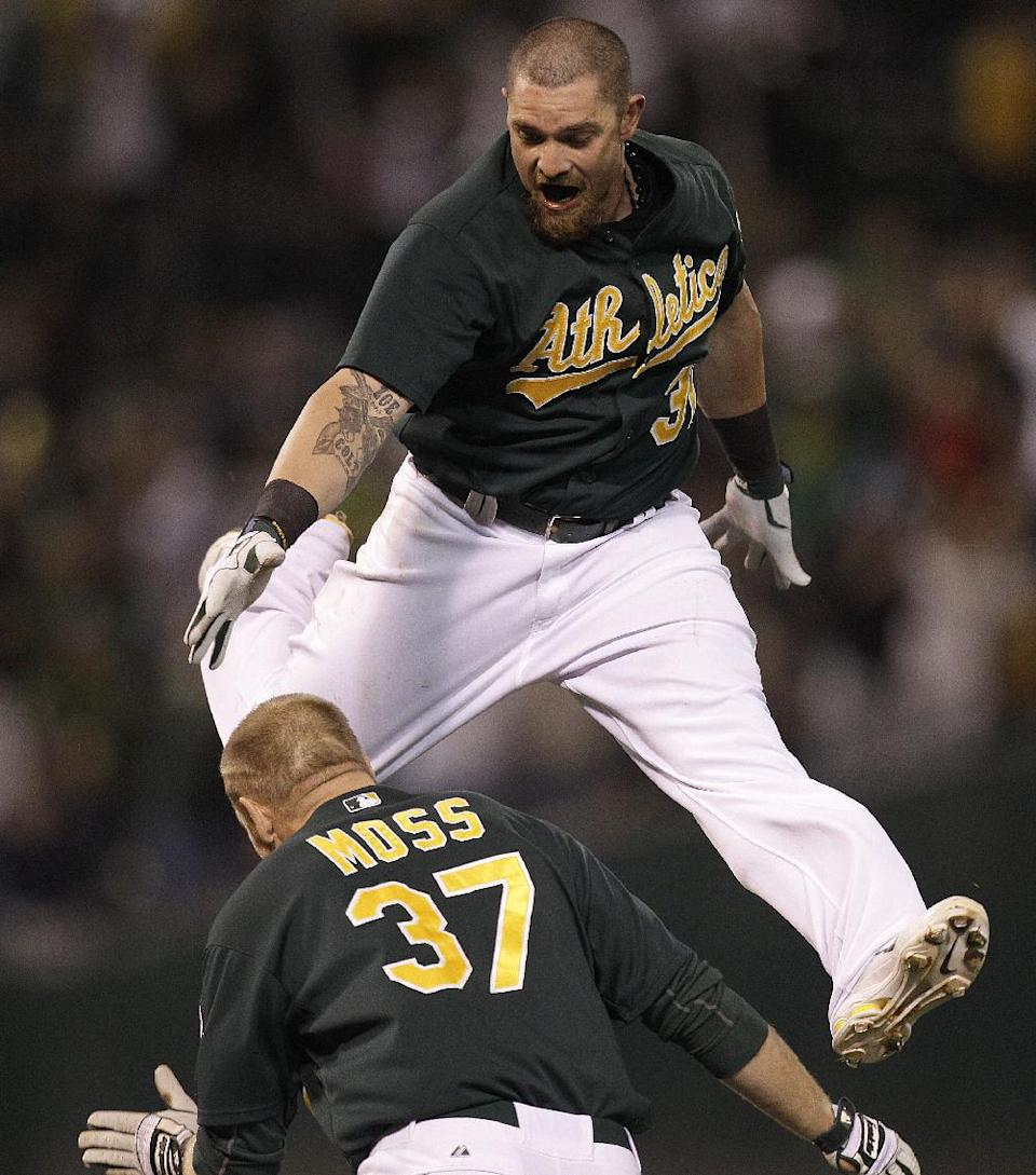 Oakland Athletics' Jonny Gomes, top celebrates with Brandon Moss (37) after Moss made the winning hit against the New York Yankees in the ninth inning of a baseball game Friday, July 20, 2012, in Oakland, Calif. (AP Photo/Ben Margot)