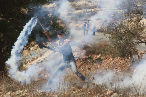 A Palestinian throws back a gas canister, previously fired by Israeli troops during a protest against the expansion of the nearby Jewish settlement of Halamish, in the West Bank village of Nabi Saleh, near Ramallah, Friday, Sept. 30, 2011. (AP Photo/Nasser Shiyoukhi)