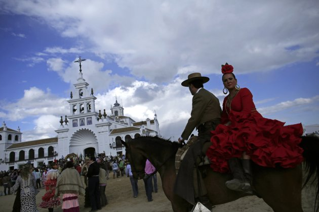 A pilgrim couple rides a horse next to the shrine of El Rocio in Almonte, southern Spain