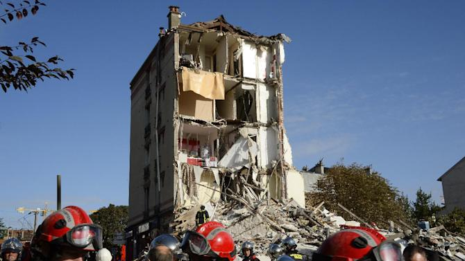 Firefighters and rescue workers inspect the site where a four-storey residential building collapsed following a blast in Rosny-sous-Bois in the eastern suburbs of Paris on August 31, 2014