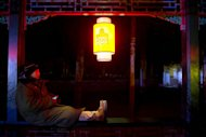 A worker uses a mobile phone as he rests beneath a lantern at the Summer Palace prior to a new year count-down event in Beijing on December 31, 2012