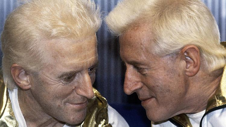 FILE - In this Dec. 17, 1986 file photo, Jimmy Savile, right, poses for photographers with a wax work model at Madame Tussauds museum in London. British police investigating sex abuse allegations against the late BBC entertainer Jimmy Savile say that they have recorded 199 crimes in which Savile is a suspect. In an update on its investigation, Scotland Yard said Wednesday Dec. 12, 2012 that 450 people have come forward with information relating to the children's television presenter, who died last year at age 84. Most of those people have alleged sexual abuse, and there were 31 rape allegations recorded against Savile, police said. (AP Photo/John Redman, File)
