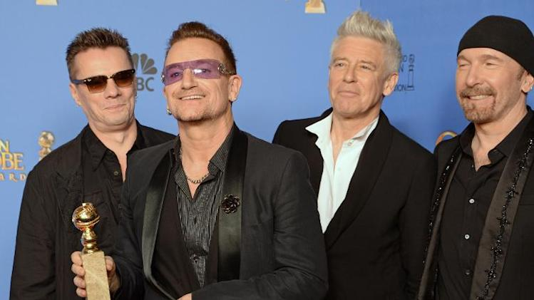 "Larry Mullen Jr.(L), Bono, Adam Clayton and The Edge of U2 after winning a Golden Globe for Best Original Song for ""Ordinary Love"" from ""Mandela: Long Walk to Freedom,"" in Beverly Hills, California, January 12, 2014"