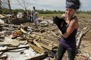 "Brittany Brown rushes to get aid after finding her grandmother's cat ""Kitty"" which was buried in tornado rubble for two days at the grandmother's destroyed home Wednesday, May 22, 2013, in Moore, Okla. Cleanup continues two days after a huge tornado roared through the Oklahoma City suburb, flattening a wide swath of homes and businesses. (AP Photo/Charlie Riedel)"