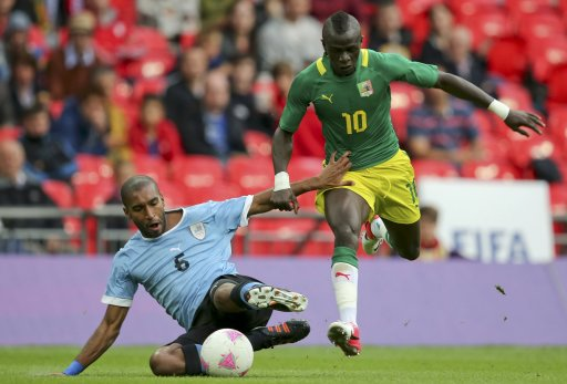 Uruguay's German Rolin challenges Senegal's Sadio Mane during their men's preliminary first round Group A soccer match at the London 2012 Olympic Games in the Wembley Stadium in London