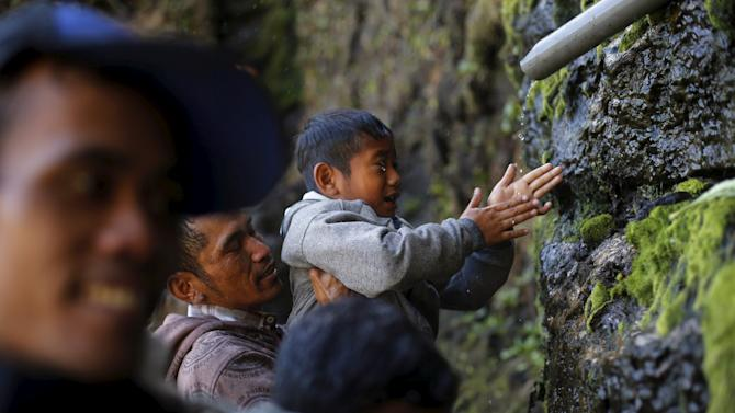 A father holds up his son as they wash their face with holy water from a stream for prayers ahead of the annual Kasada festival at Mount Bromo
