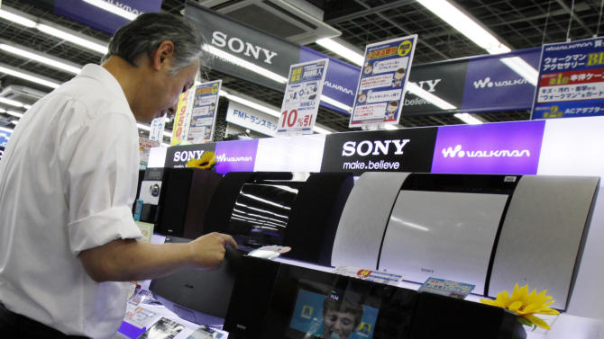 A shopper tries a Sony's product at a store in Tokyo, Thursday, Aug. 2, 2012. Sony is reporting a bigger loss for the April-June quarter at 24.6 billion yen ($316 million) despite a sales recovery from a disaster-struck previous year. (AP Photo/Koji Sasahara)