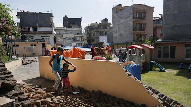 A young girl walks with a boy over a collapsed school playground in Kathmandu, Nepal, Monday, April 27, 2015. A strong magnitude 7.8 earthquake shook Nepal's capital and the densely populated Kathmandu Valley on Saturday, causing extensive damage with toppled walls and collapsed buildings. (AP Photo/Wally Santana)
