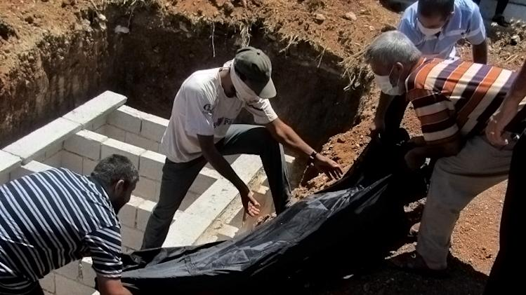 This citizen journalism image provided by Shaam News Network SNN, taken on Thursday, Aug. 9, 2012, purports to show Syrians burying a body in Daraa, Syria. (AP Photo/Shaam News Network, SNN)THE ASSOCIATED PRESS IS UNABLE TO INDEPENDENTLY VERIFY THE AUTHENTICITY, CONTENT, LOCATION OR DATE OF THIS CITIZEN JOURNALIST IMAGE
