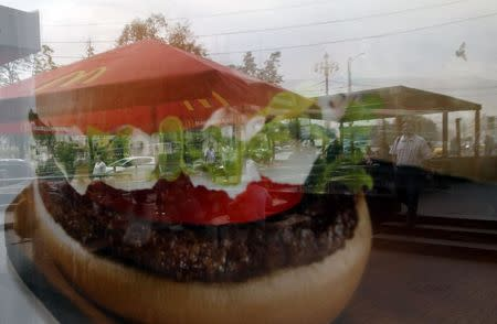 People are reflected in a window of a closed McDonald's restaurant in Moscow