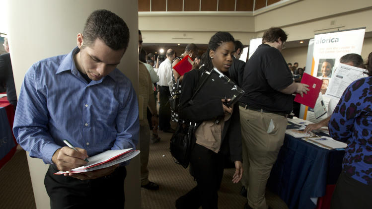 In this Tuesday, Jan. 22, 2013 photo, Fernando Rames answers questions on a job application at the job fair in Sunrise, Fla. U.S. employers added 157,000 jobs in January, and hiring was much stronger at the end of 2012 than previously thought, providing reassurance that the job market held steady even as economic growth stalled, according to Labor Department reports, Friday, Feb. 1, 2013. (AP Photo/J Pat Carter)