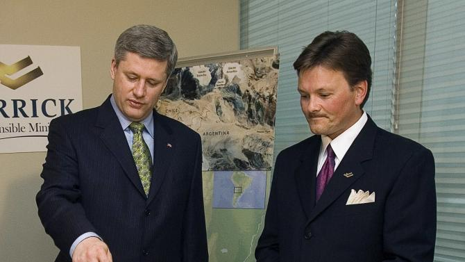 FILE - In this July 18, 2007 file photo, Canada's Prime Minister Stephen Harper, left, is shown a model of Barrick's Pascua Lama mining project by Barrick's Igor Gonzalez during a visit to the company's office in Santiago, Chile. A Chilean court's halted on April 10, 2013 the construction of Barrick Gold Corp.'s $8 billion, border-straddling mine on the high-altitude spine of the Andes. Chile's environmental and mining ministries are on record supporting the suspension, which is based on allegations that construction is kicking up dust that has settled on the nearby Toro 1, Toro 2 and Esperanza glaciers, hastening their retreat, and threatening the Estrecho river, which supplies water to the Diaguita tribe living downstream. (AP Photo/Ryan Remiorz, CP, File)
