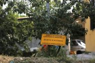 "A sign which reads, ""Prohibited to enter. Under close weapon surveillance"" at an orchard confiscated from the Camorra clan, or the local mafia, in Chiaiano next to Scampia, district of northern Naples, August 21, 2013. REUTERS/Alessandro Bianchi"