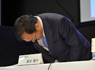 Japan's electronics company Sharp President Takashi Okuda bows his head as he leaves a press conference in Tokyo. Sharp said it will cut 5,000 jobs by March 2013 as it reported a quarterly loss and said it would remain in the red for the rest of the year