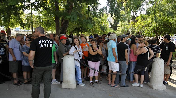 People wait in a line to receive products from the members of Greece's extreme right Golden Dawn party at Athens' main Syntagma Square, opposite parliament, on Wednesday, Aug. 1, 2012. The volunteers checked ID cards of the public before handing Greek citizens food that included milk cartons, pasta, potatoes and olive oil. Golden Dawn won 18 seats in the 300-seat parliament in June general elections. Senior party members openly support a policy of granting Greek citizenship based on racial identity. The party has stepped up its charity effort as Greece is suffering through a fifth year of recession, with rapidly rising rates of poverty and unemployment. (AP Photo/Thanassis Stavrakis)