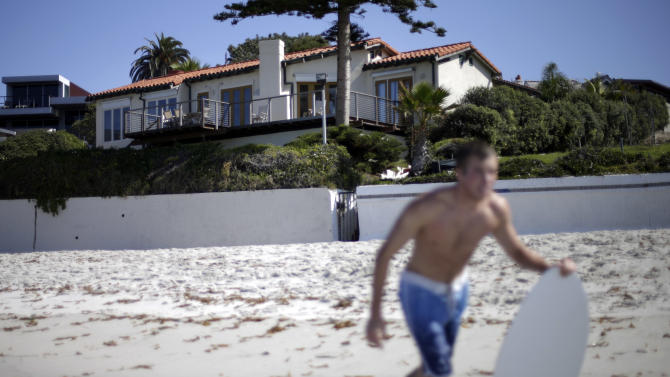 John Pukstas runs towards the surf with his skimboard on a beach in front of a home owned by former presidential candidate Mitt Romney, and his wife Ann, Friday, Oct. 11, 2013, in La Jolla, Calif. The California Coastal Commission voted Friday to allow the Romneys to move forward with plans to raze their La Jolla beachfront home and replace it with an 11,000-square-foot mansion. (AP Photo/Gregory Bull)